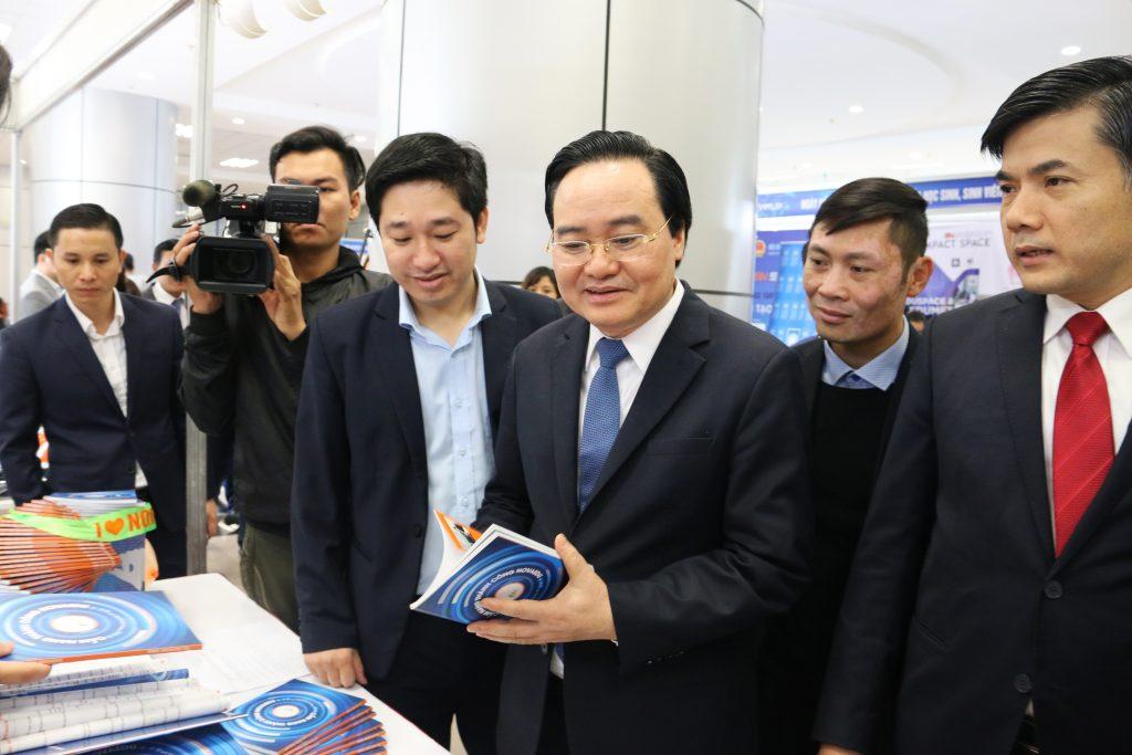 """Bộ trưởng bộ Giáo dục và Đào tạo Phùng Xuân Nhạ cầm trên tay cuốn """"Cẩm nang thành công"""" của Novaedu."""